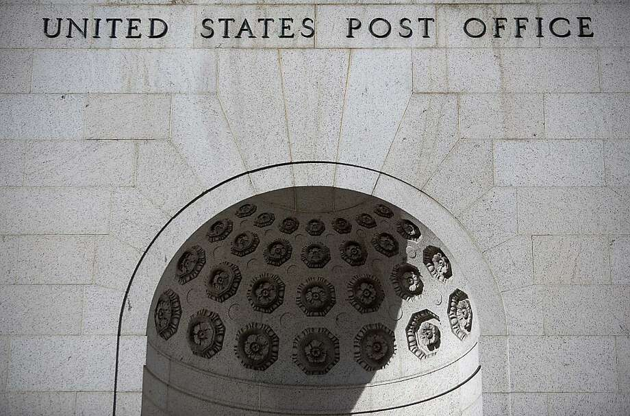 "The words ""United States Post Office"" are displayed on the facade of The James A. Farley Building post office in New York, U.S., on Thursday, Nov. 15, 2012. The U.S. Postal Service said its net loss last year widened to $15.9 billion, more than the $15 billion it had projected, as mail volume continued to drop, falling 5 percent. Photograph: Victor J. Blue/Bloomberg Photo: Victor J. Blue, Bloomberg"