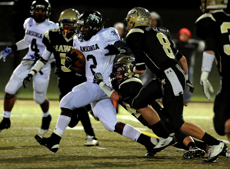 Ansonia's #2 Arkeel Newsome makes his way to the endzone for a touchdown with a Woodland player in tow, during NVL football championship action action in Waterbury, Conn. on Thursday November 14, 2012. Photo: Christian Abraham / Connecticut Post