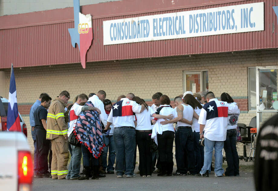 Parade participants and public safety officials huddle after a trailer carrying wounded veterans in a parade was struck by a train in Midland. Photo: James Durbin, Associated Press / Reporter-Telegram