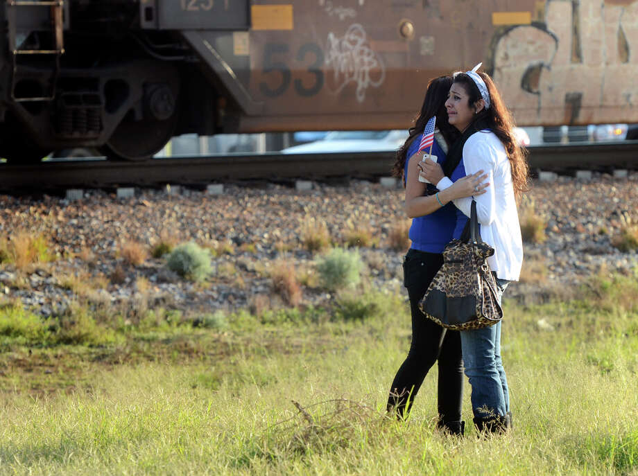 "Parade participants react after a trailer carrying wounded veterans in a parade was struck by a train in Midland, Texas, Thursday, Nov. 15, 2012. ""Show of Support"" president and founder Terry Johnson says there are ""multiple injuries"" after a Union Pacific train slammed into the trailer, killing at least four people and injuring 17 others. (AP Photo/Reporter-Telegram, James Durbin) Photo: James Durbin, Associated Press / Reporter-Telegram"