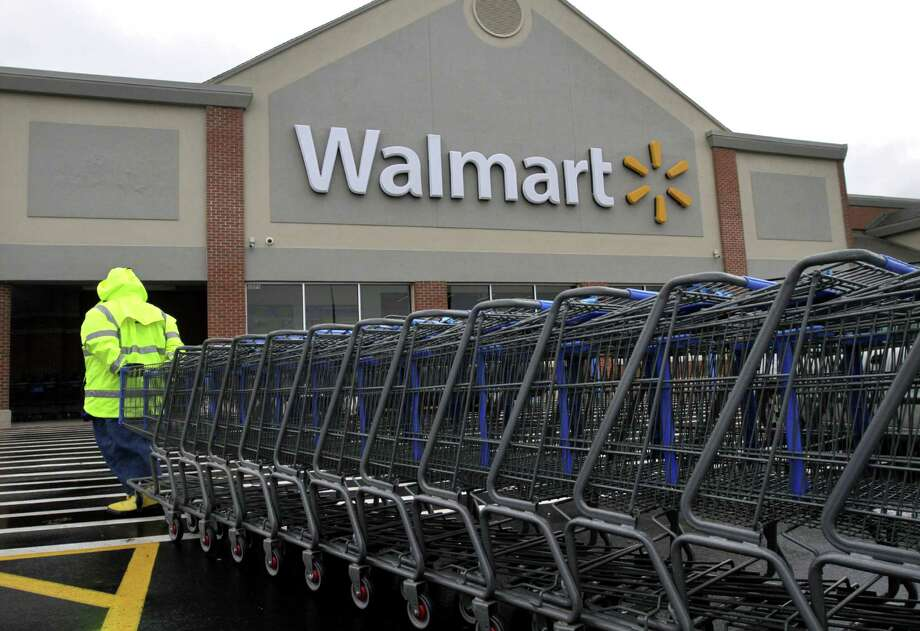 In this Tuesday, Nov. 13, 2012 photo a worker pulls a line of shopping carts toward a Walmart store in North Kingstown, R.I. Wal-Mart Stores Inc. reported a 9 percent increase in net income for the third quarter, but revenue for the world's largest retailer fell below Wall Street forecasts as its low-income shoppers continue to grapple with an uncertain economy. (AP Photo/Steven Senne) Photo: Steven Senne