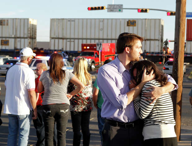 "Bystanders react as emergency personnel work the scene where a trailer carrying wounded veterans in a parade was struck by a train in Midland, Texas, Thursday, Nov. 15, 2012. ""Show of Support"" president and founder Terry Johnson says there are ""multiple injuries"" after a Union Pacific train slammed into the trailer, killing at least four people and injuring 17 others. (AP Photo/Reporter-Telegram, James Durbin) Photo: James Durbin, Associated Press / Reporter-Telegram"
