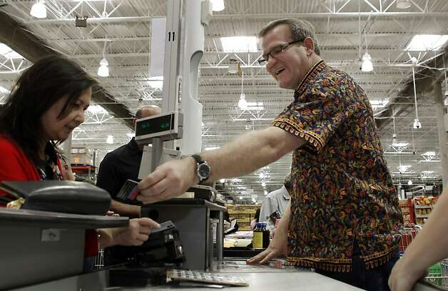 Mark Gilliam, a cashier at the San Francisco, Calif.,  Costco, helps Donna Fujii at his register on Tuesday, November 13, 2012. Gilliam is a former airline flight attendant who left the business in 2007 when Northwest was bought by Delta. During his 17 years in the air he flew mostly to Asia, and learned to speak siome Japanese, Tagalog, Mandarin, Cantonese, Thai and Korean. He says he gets to use each of those languages regularly since a large percentage of Costco's clientele is Asian. Photo: Carlos Avila Gonzalez, The Chronicle