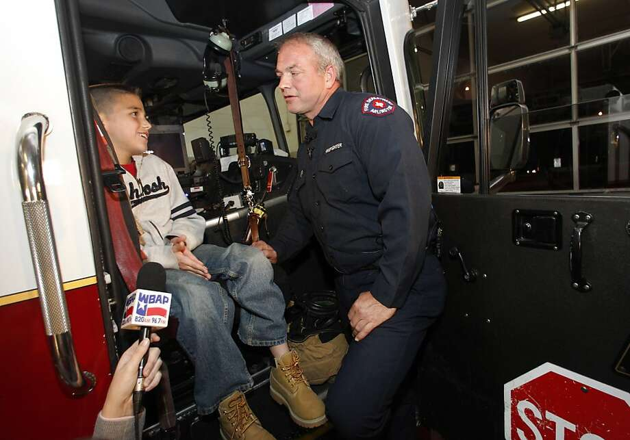 Koregan Quintanilla, 10, visits firefighter Wesley Keck at the station in Arlington, Texas, where the boy was legally abandoned as an infant. Photo: Tony Gutierrez, Associated Press