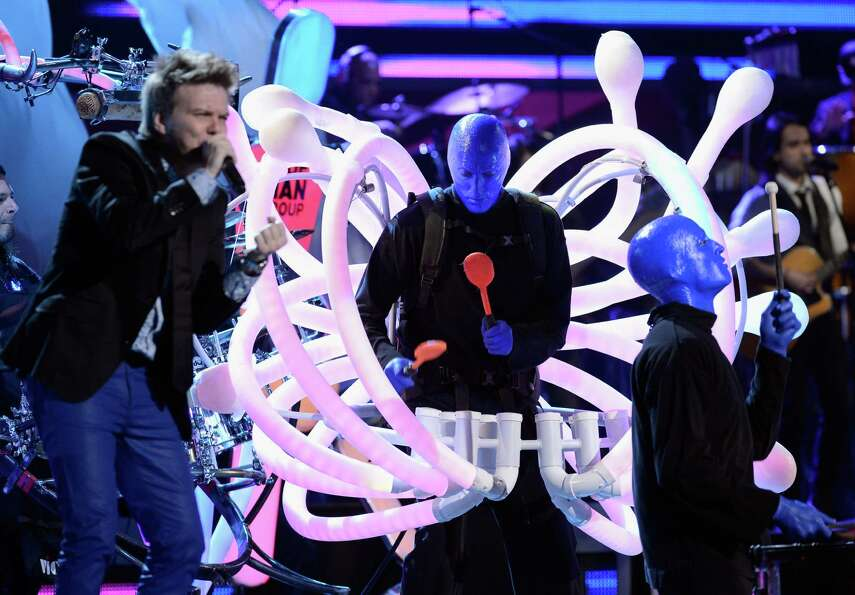Singer Michel Telo (L) and Blue Man Group perform onstage during the 13th annual Latin GRAMMY Awards