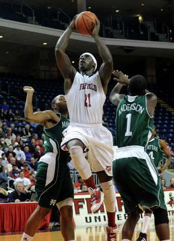 Fairfield University's #21 Rakim Sanders goes up to the net between two Manhattan College players, during men's basketball action at the Webster Bank Arena in Bridgeport, Conn. on Thursday February 9, 2012. Photo: Christian Abraham / Connecticut Post