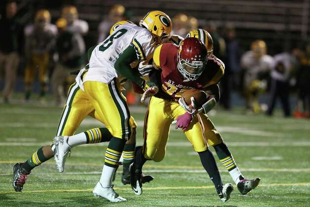Mike Ross Connecticut Post freelance -St. Joseph's #32 Mufasa Abdul-Basir drags three Trinity Catholic High School defenders into the endzone for a score during first half action on Thursday evening. Photo: Mike Ross / Connecticut Post Freelance