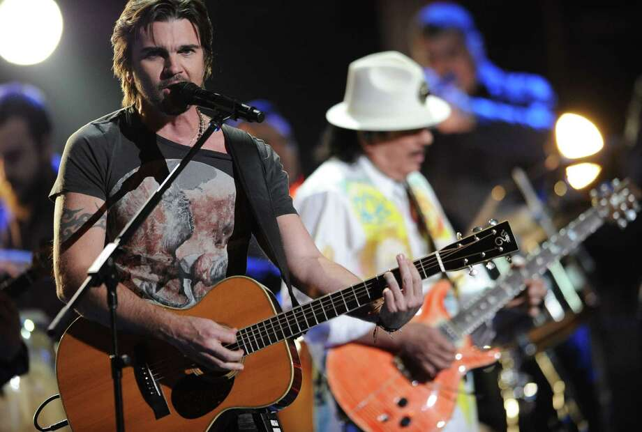 "Juanes, left, and Santana, in background, perform ""Fijate Bien"" at the 13th Annual Latin Grammy Awards at Mandalay Bay on Thursday, Nov. 15, 2012, in Las Vegas. (Photo by Al Powers/Powers Imagery/Invision/AP) Photo: Al Powers, Associated Press / Invision"