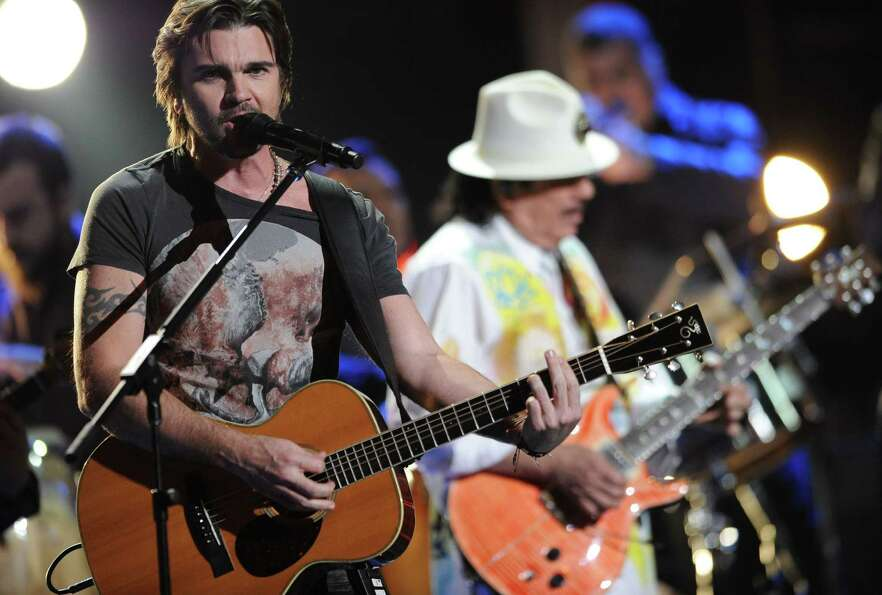 Juanes, left, and Santana, in background, perform