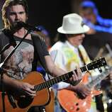 """Juanes, left, and Santana, in background, perform """"Fijate Bien"""" at the 13th Annual Latin Grammy Awards at Mandalay Bay on Thursday, Nov. 15, 2012, in Las Vegas. (Photo by Al Powers/Powers Imagery/Invision/AP)"""