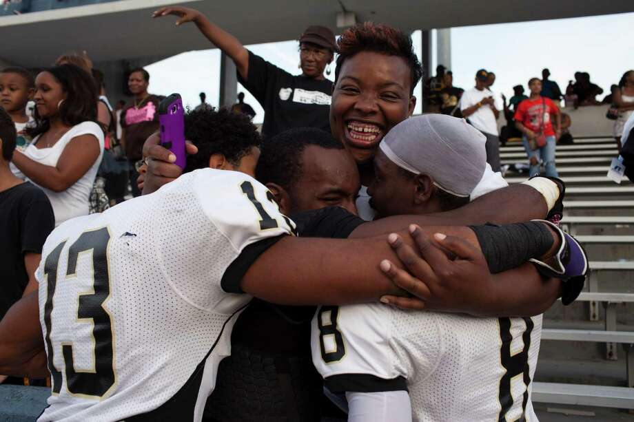 Shonta Jackson, the mother of a football player, hugs her son Demarcus Jackson, right, and two other players after North Forest ISD defeated Wheatley High School Nov. 10, 2012 in Houston at Barnett Stadium. North Forest won and is now 10-0 - they won 4 games last season and just two the year before that. North Forest leaders are fighting to keep the state from closing their school district next year unless they can raise student test scores, lower the dropout rate, repay $8 million in debt and don't deplete the savings account again. Photo: Eric Kayne, For The Chronicle / © 2012 Eric Kayne