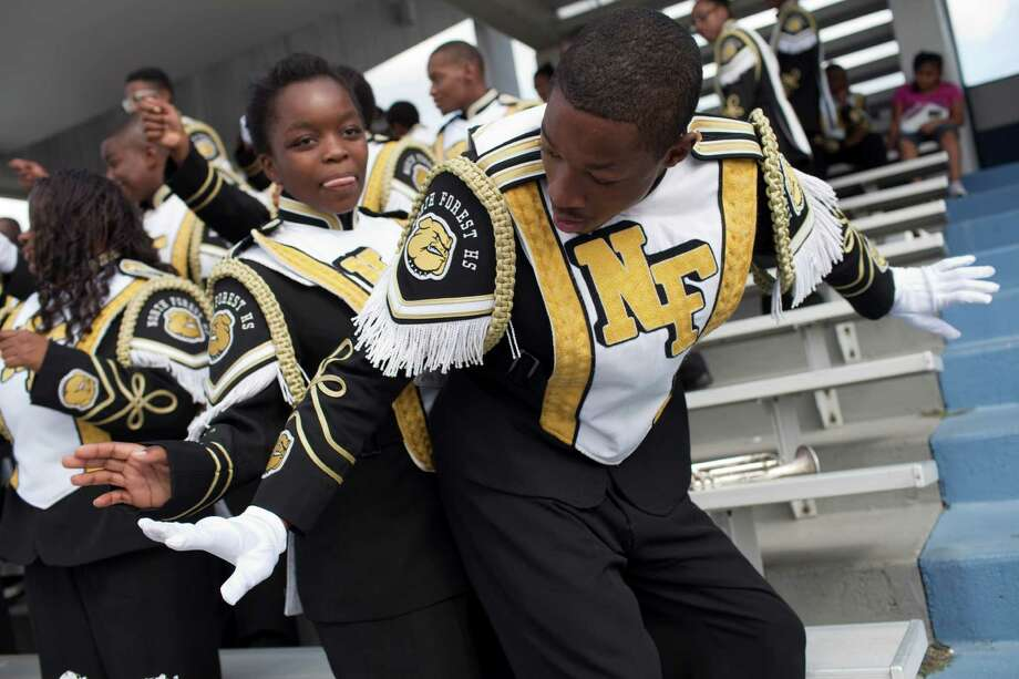 North Forest ISD band members Sandrine Ntanyosha, 15, left, and Jarvis Dillard, 15 dance as their football team plays Wheatley High School Nov. 10, 2012 in Houston at Barnett Stadium. North Forest won and is now 10-0 - they won 4 games last season and just two the year before that. North Forest leaders are fighting to keep the state from closing their school district next year unless they can raise student test scores, lower the dropout rate, repay $8 million in debt and don't deplete the savings account again. Photo: Eric Kayne, For The Chronicle / © 2012 Eric Kayne