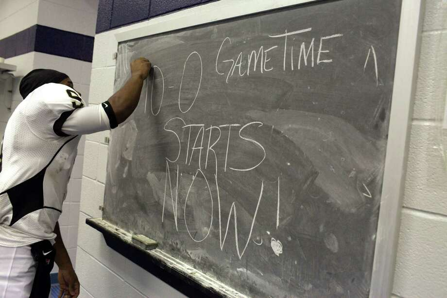 North Forest ISD football player LonDarius Thomas writes on a chalk board inside the locker room as North Forest ISD plays Wheatley High School Nov. 10, 2012 in Houston at Barnett Stadium. North Forest leaders are fighting to keep the state from closing their school district next year unless they can raise student test scores, lower the dropout rate, repay $8 million in debt and don't deplete the savings account again. Photo: Eric Kayne, For The Chronicle / © 2012 Eric Kayne