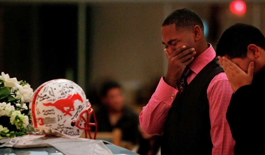 Joseph Hearne, 16, weeps before the remains of friend Luis Daniel Garrido, a Memorial High School football player, after attending the funeral mass at St. Jerome Catholic Church on Thursday, Nov. 15, 2012, in Houston. Luis Garrido was a beloved football player at Memorial High School who, along with his father, was killed by a drunk driver over the weekend. The Memorial community has come together to help his mother cope emotionally and financially. Photo: Mayra Beltran, Houston Chronicle / © 2012 Houston Chronicle