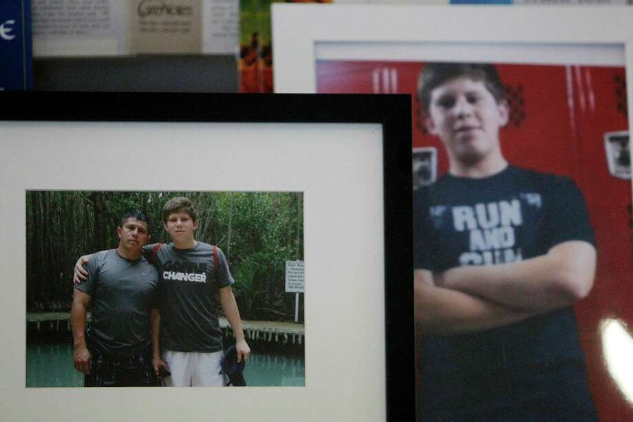 Photos of Luis Marcial Garrido and son Luis Daniel Garrido, Memorial High School Football player, are on display during the Funeral Mass at St. Jerome Catholic Church on Thursday, Nov. 15, 2012, in Houston. Both were killed by a drunk driver over the weekend. Photo: Mayra Beltran, Houston Chronicle / © 2012 Houston Chronicle