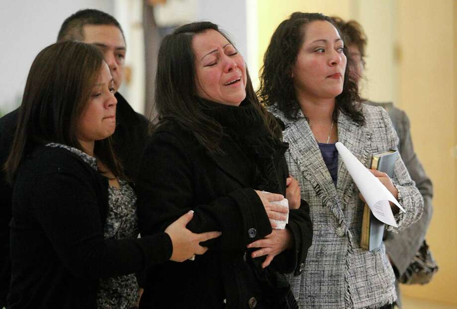 Miriam Garrido mourns the loss of her husband Luis Marcial Garrido and son Luis Daniel Garrido. Photo: Mayra Beltran, Houston Chronicle / © 2012 Houston Chronicle