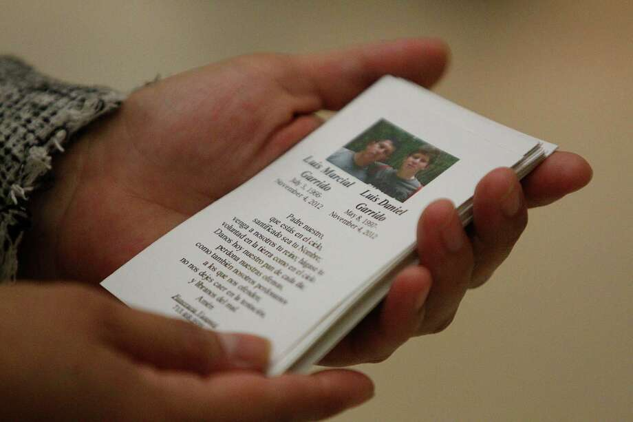 A prayer accompanies the photograph of Luis Marcial Garrido and son Luis Daniel Garrido, handed out before the Funeral Mass at St. Jerome Catholic Church. Photo: Mayra Beltran, Houston Chronicle / © 2012 Houston Chronicle
