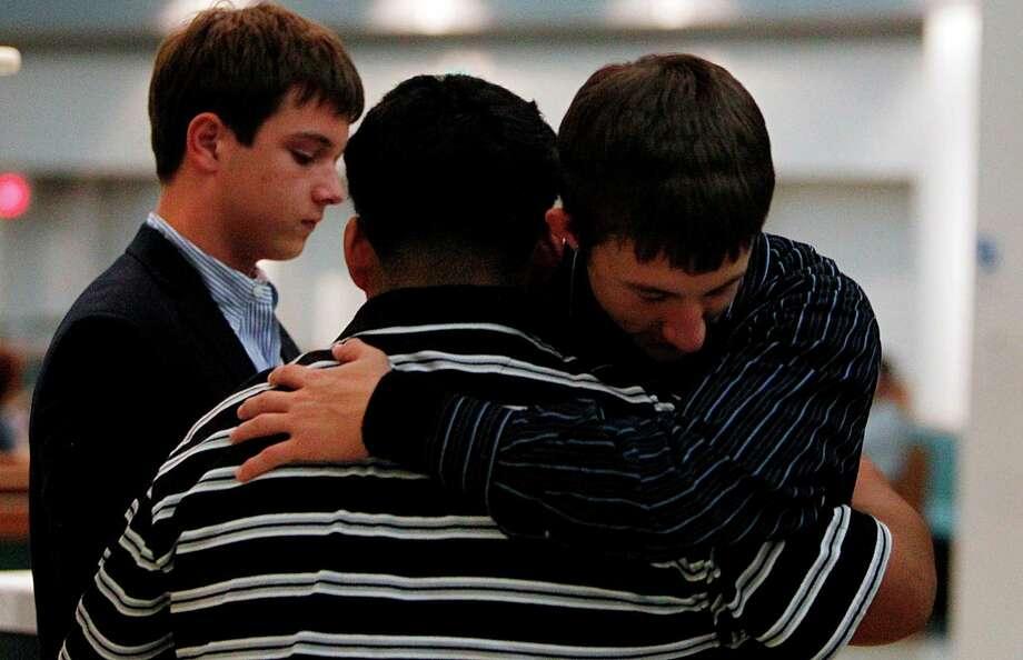 Edwin DeCora, 15, embraces Jose Martinez, 15, after the funeral mass of Luis Daniel Garrido. Photo: Mayra Beltran, Houston Chronicle / © 2012 Houston Chronicle