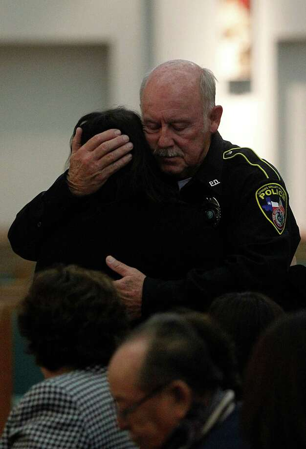 Police Officer Denis Book embraces family friend Miriam Garrido after the funeral mass for Memorial High School football player Luis Daniel Garrido and father Luis Marcial Garrido at St. Jerome Catholic Church. Photo: Mayra Beltran, Houston Chronicle / © 2012 Houston Chronicle