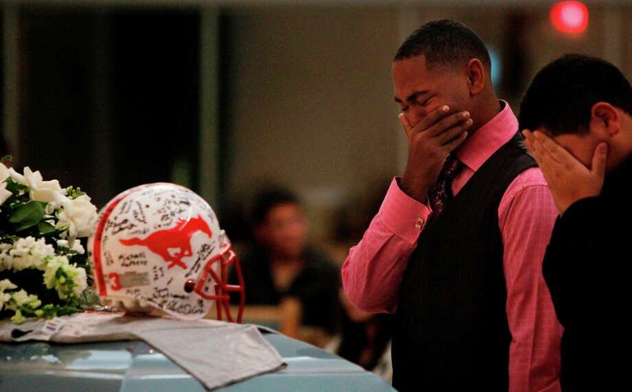 Joseph Hearne, 16, weeps at the casket of friend Luis Garrido, a Memorial High football player who died in a wreck. Photo: Mayra Beltran, Staff / © 2012 Houston Chronicle