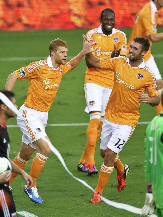 Andre Hainault, left, celebrates his game-tying goal with Will Bruin on Sunday against D.C. United. Hainault has come up big in the playoffs the past two years. Photo: Nick De La Torre, Staff / © 2012  Houston Chronicle