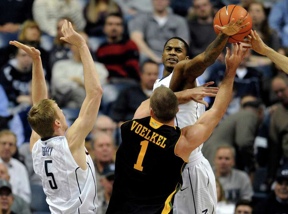 Connecticut's Phillip Nolan, right, stops a shot attempt by Vermont's Brian Voelkel (1) as Connecticut's Niels Giffey (5) defends in the first half of an NCAA college basketball game in Storrs, Conn., Tuesday, Nov. 13, 2012. (AP Photo/Jessica Hill) Photo: Jessica Hill, Associated Press / FR125654 AP