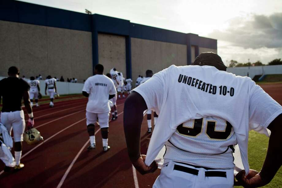 North Forest football players walk off the field at Barnett Stadium wearing T-shirts commemorating a perfect regular season. The Bulldogs set a goal to go undefeated this season and accomplished it with an 81-14 win over Wheatley last Saturday. Photo: Eric Kayne / © 2012 Eric Kayne