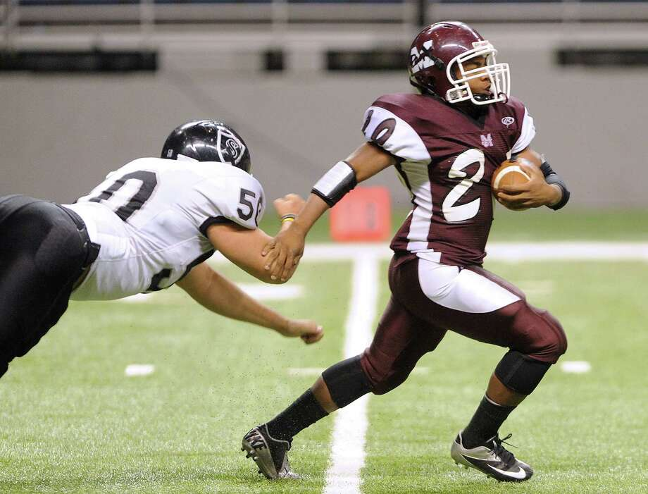 Running back Tre Scallion of Marshall eludes Mason Martinez (50) of Steele during Class 5A Division II bidistrict playoff action at the Alamodome on Thursday, Nov. 15, 2012. Photo: Billy Calzada, Express-News / © 2012 San Antonio Express-News