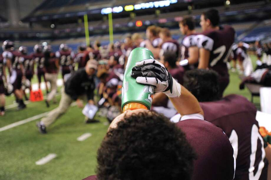A member of the Marshall Rams refreshes himself on the sideline during Class 5A Division II bidistrict playoff action against Steele at the Alamodome on Thursday, Nov. 15, 2012. Photo: Billy Calzada, Express-News / © 2012 San Antonio Express-News