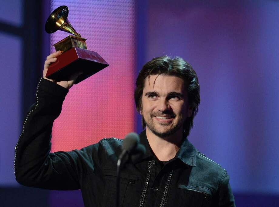 Juanes holds up his trophy during the 13th Annual Latin Grammy show on November 15, 2012 in Las Vegas, Nevada.    AFP PHOTO/Robyn BECKROBYN BECK/AFP/Getty Images Photo: ROBYN BECK, Getty Images / AFP