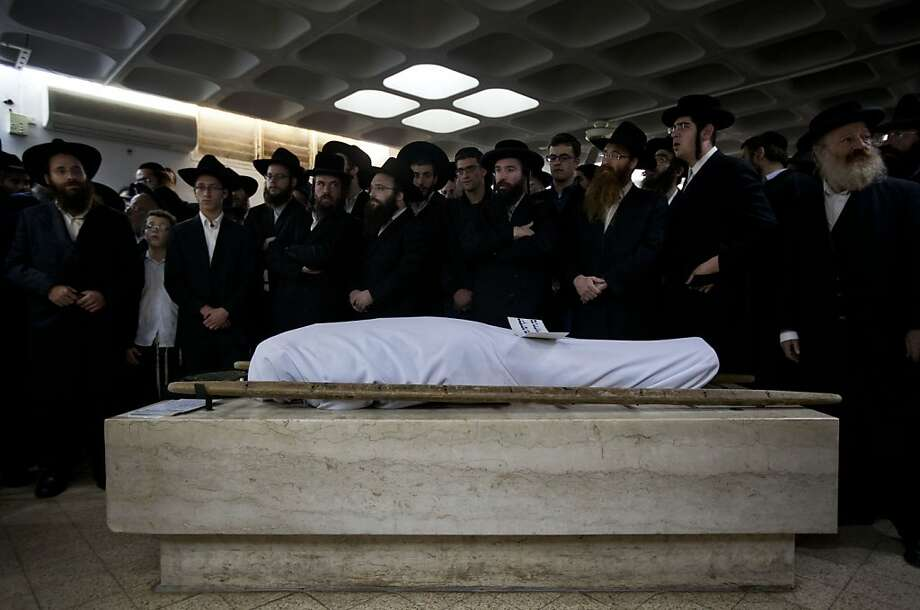 Ultra Orthodox Jewish men gather around the body of Mirah Sharf that was killed in the southern town of Kiryat Malachi by a rocket thought to have been fired by Palestinian militants from the Gaza Strip, during her funeral in Jerusalem, Thursday, Nov. 15, 2012.  Gaza militants led by the ruling Hamas Islamic group showered Israel with rockets Thursday in apparent retaliation for Israel's assassination of Hamas' powerful military chief a day before, and Israel's airforce struck dozens of Hamas-linked targets in Gaza with missiles on Thursday. Photo: Sebastian Scheiner, Associated Press