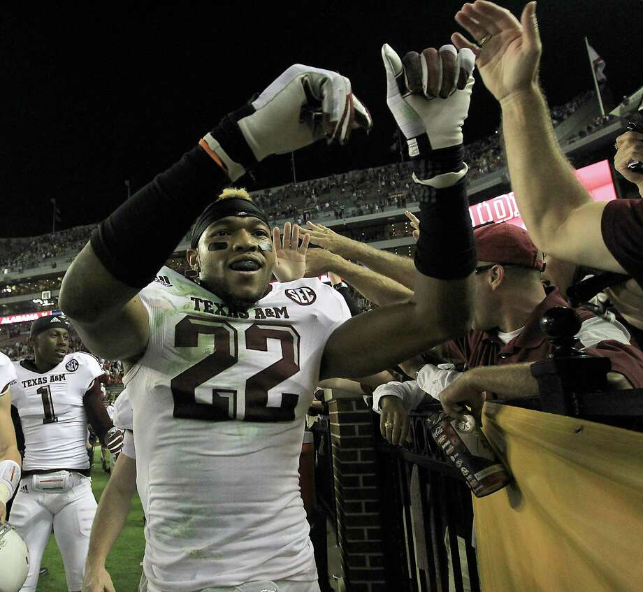 Texas A&M defensive back Dustin Harris (22) high-five fans as he and fellow teammates celebrate after beating Alabama during a college football game at Bryant-Denny Stadium, Saturday, Nov. 10, 2012, in Tuscaloosa.  ( Karen Warren / Houston Chronicle ) Photo: Karen Warren, Staff / © 2012  Houston Chronicle