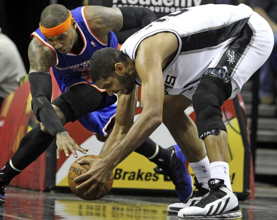 Tim Duncan grabs a loose ball as Carmelo Anthony circle around then fouls as San Antonio hosts the New York Knicks at the AT&T Center on November 15, 2012. (Tom Reel / San Antonio Express-News)