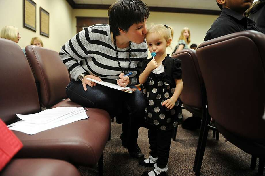 Heidi Kellums gives her new adopted daughter Breanah, 3, as kiss as she finishes paper work after Breanah's adoption at the Evansville Adoption Day celebration at the Civic Center on Thursday, Nov. 15, 2012 in Evansville, Ind. Heidi and her husband Larry have four biological  kids and Breanah makes the couples sixth adopted child. The children who range in ages 18-3 feel that Breanah completes their family. She has had a lot of medical problems and every one of the couples children adore and help out with Breanah's care. Photo: Erin McCracken, Associated Press