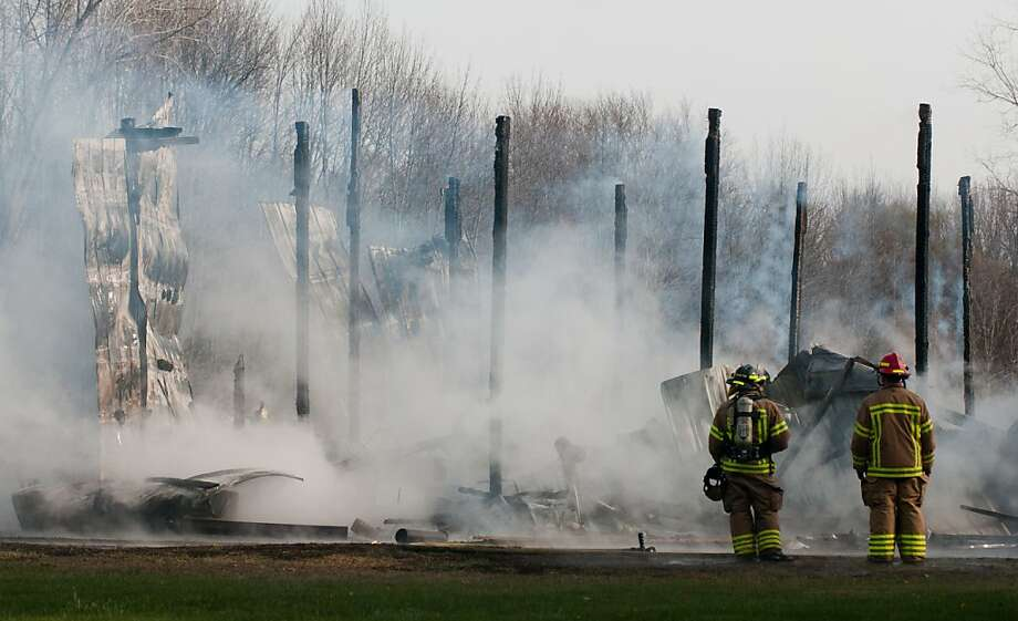 Firefighters pull down the sides of a barn to control the fire at 2405 S. Garfield in Beaver Township, Mich., Thursday, Nov. 15, 2012. No one was injured, but the structure was destroyed. Photo: Yfat Yossifor, Associated Press