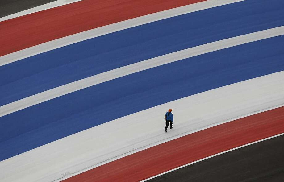 A pedestrian moves across the track at the Circuit of the Americas race track on Thursday, Nov. 15, 2012, in Austin, Texas. Formula One's U.S. Grand Prix auto race is scheduled for Sunday. Photo: Eric Gay, Associated Press