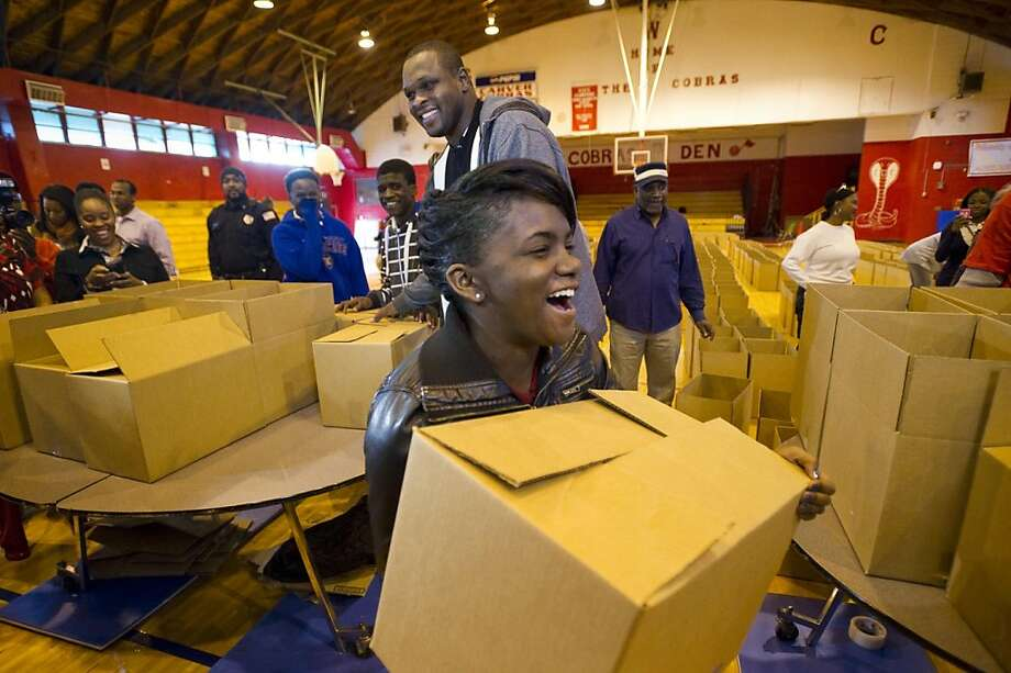 Antrice Boyd laughs after receiving the first of 400 boxed Thanksgiving meals from Memphis Grizzlies forward Zach Randolph during a giveaway to the families of students at Carver High School Thursday, Nov. 15, 2012. Randolph paid for the meals himself, which included ham, stuffing, canned vegetables, macaroni and cheese, and dessert mix, as part of the Grizzlies' Season of Giving effort. Photo: Brandon Dill, Associated Press