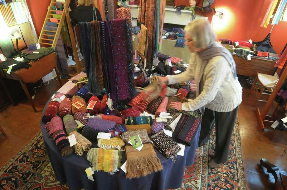Guild member Anna Bierma straightens up some scarves for sale at the Hudson-Mohawk Weavers' Guild Show and Sale at  the historic Pruyn House on Thursday, Nov. 15, 2012 in Latham, NY.  The show runs through Sunday.  The show consists of handwoven items from home goods like rugs and table linens to clothing, accessories and holiday gifts.  Admission is free.   (Paul Buckowski / Times Union) Photo: Paul Buckowski