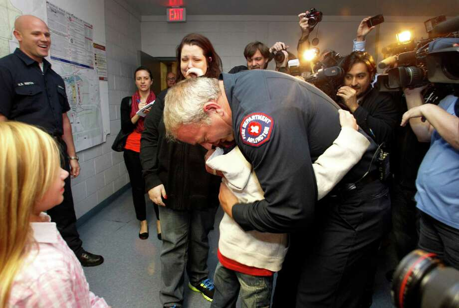 Rebecca Quintanilla, center left, wipes tears from her face as her adopted son Koregan, 10, hugs Arlington Fire Fighter Wesley Keck, center right, as the two meet Thursday, Nov. 15, 2012, in Arlington, Texas. A Texas boy abandoned at a fire station as an infant got his wish for his 10th birthday: to meet the firefighter who saved him. On Thursday evening, the boy was to celebrate his recent birthday by meeting Arlington firefighter Wesley Keck, riding on a fire truck and touring the station. (AP Photo/Tony Gutierrez) Photo: Tony Gutierrez, STF / AP