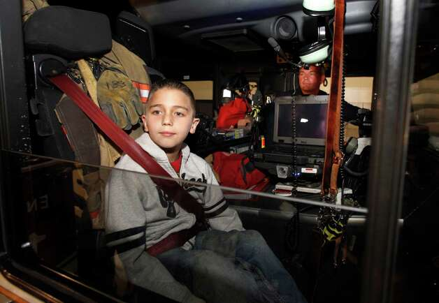 Koregan Quintanilla, 10, of Watauga, Texas, looks out the passenger window of a Arlington Fire Department fire truck as firefighter Wesley Keck, rear, prepares to take him on a short trip around the neighborhood Thursday, Nov. 15, 2012, in Arlington, Texas. Quintanilla, who was abandoned at a fire station as an infant, celebrated his recent birthday by meeting Keck, the firefighter who saved him, riding on a fire truck and touring the station. (AP Photo/Tony Gutierrez) Photo: Tony Gutierrez, STF / AP