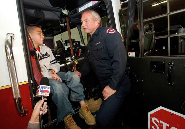 Koregan Quintanilla, 10, of Watauga, Texas, left, talks to firefighter Wesley Keck as they prepare to take a short trip around the neighborhood on a fire truck Thursday, Nov. 15, 2012, in Arlington, Texas. Quintanilla, who was abandoned at a fire station as an infant, celebrated his recent birthday by meeting Keck, the firefighter who saved him, riding on a fire truck and touring the station. (AP Photo/Tony Gutierrez) Photo: Tony Gutierrez, STF / AP
