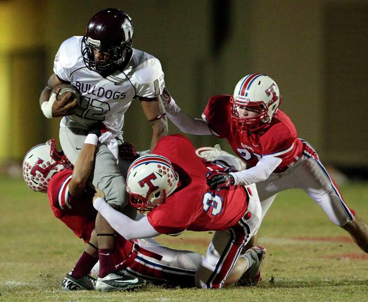 Reagan wide out Malcolm LaFleur (12) is gang tackled by three Tomball defenders after making a catch