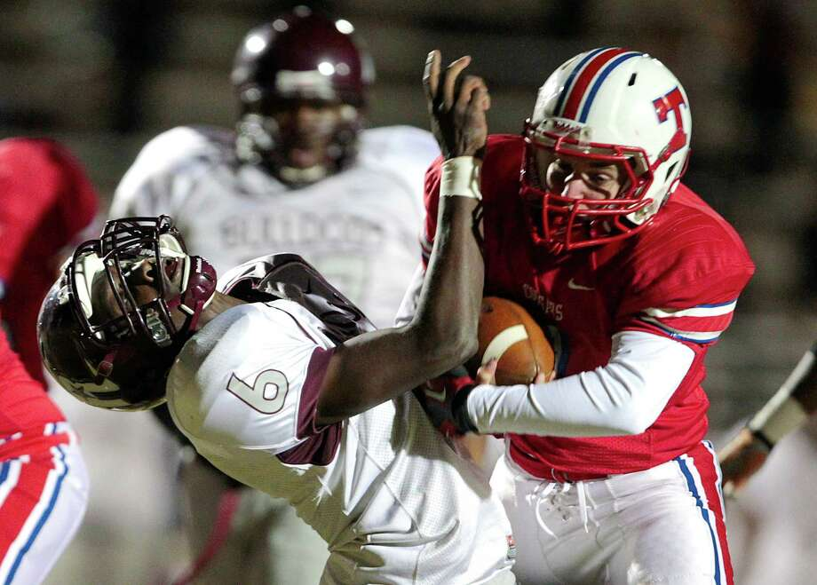 Reagan free safety Byron Washington (6) is knocked back by Tomball quarterback Drew Reynolds (7)  in the first half of Tomball and Reagan  Class 4A Division I playoff match-up at Tomball Independent School District Stadium. Thursday, Nov. 15, 2012, in Tomball. Photo: Billy Smith II, Houston Chronicle / © 2012 Houston Chronicle