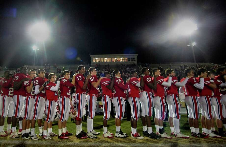 Members of the  Tomball High school football team line up for the National Anthem under the lights before the start of Tomball and Regan  Class 4A Division I playoff match-up at Tomball Independent School District Stadium. Thursday, Nov. 15, 2012, in Tomball. Photo: Billy Smith II, Houston Chronicle / © 2012 Houston Chronicle