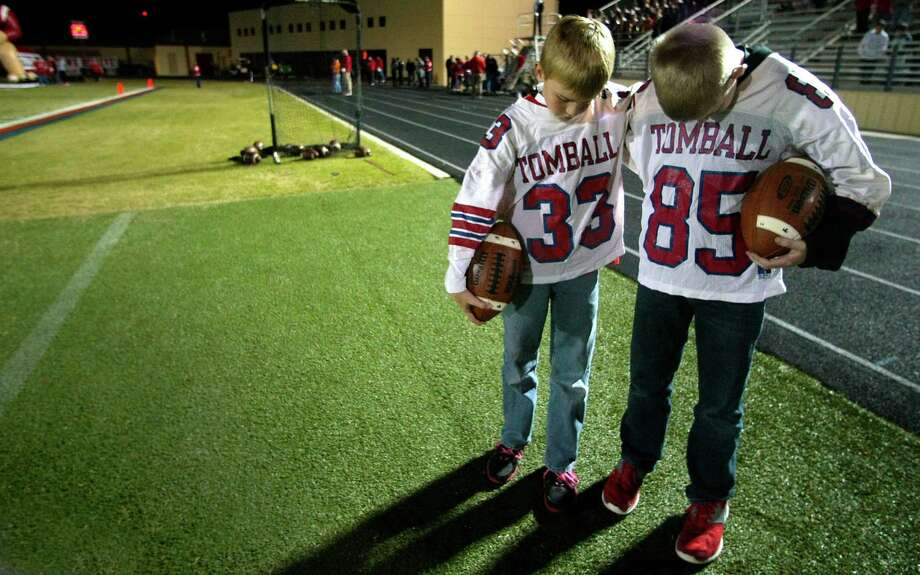 (l-r) Tomball ball boys Jacob Van Sant and Ethan Quigley bow there heads for a moment of silence before the  first half of Tomball and Reagan  Class 4A Division I playoff match-up at Tomball Independent School District Stadium. Thursday, Nov. 15, 2012, in Tomball. Photo: Billy Smith II, Houston Chronicle / © 2012 Houston Chronicle