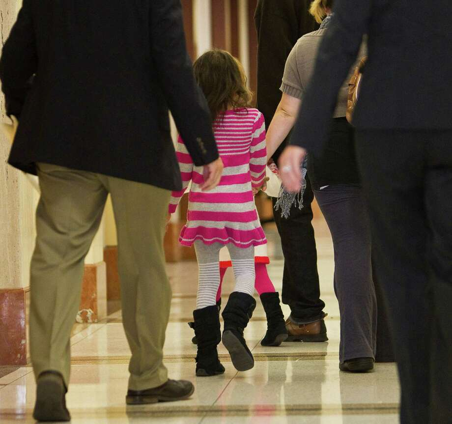 A seven year old girl, in a pink striped dress in the middle, leaves Project Court #1 after testifying in the Jessica Tata trial, Thursday, Nov. 15, 2012, in the Harris County Criminal Justice Center in Houston. Jessica Tata is convicted of murder after a fire at her home day care killed four children. ( Nick de la Torre / Houston Chronicle ) Photo: Nick De La Torre, Staff / © 2012  Houston Chronicle