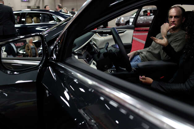 Joe Lyons looks at a 2013 Cadillac XTS with the help of Cadillac product specialist Ashley Jackson during the San Antonio Auto and Truck Show at the Henry B. Gonzalez Convention Center on Thursday, Nov. 15, 2012. Photo: Lisa Krantz, San Antonio Express-News / © 2012 San Antonio Express-News