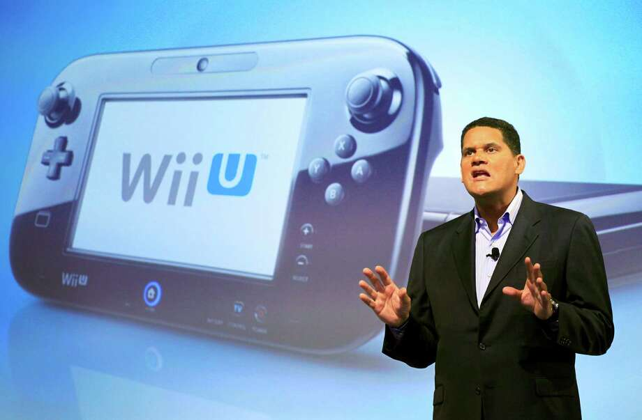 FILE - In this Sept. 13, 2012 photo, Reggie Fils-Aime, president and chief operating officer of Nintendo of America, discusses the upcoming Wii U gaming console, in New York. Much like the iPad, the curvey GamePad features a touchscreen that can be manipulated with the simple tap or swipe of a finger, but it's surrounded by the kinds of buttons, bumpers, thumbsticks and triggers that are traditionally found on a modern-day game controller. The gaming console will start at $300 and go on sale in the U.S. on Sunday, Nov. 18, in time for the holidays, the company said. (AP Photo/Mark Lennihan, File) Photo: Mark Lennihan