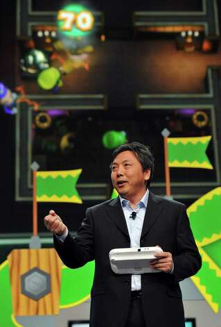 "FILE - In this June 5, 2012 publicity file photo provided by Nintendo of America, Katsuya Eguchi, Producer of Software Development for Nintendo, shows off ""Luigi's Ghost Mansion,"" one of 12 attractions in Nintendo Land, an upcoming game for the new Wii U home console, during the Nintendo All-Access Presentation at E3 2012 in Los Angeles. The Wii U GamePad controller makes asymmetric gameplay possible by allowing for multiple experiences in the same game at the same time. (AP Photo/Nintendo of America, Vince Bucci, File) Photo: Vince Bucci"