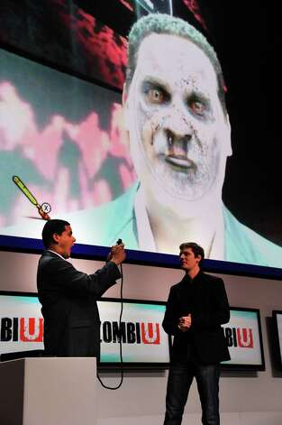 "FILE - In this June 5, 2012 publicity file photo provided by Nintendo of America, Reggie Fils-Aime, Nintendo of America's President and Chief Operating Officer, left, tests out an interactive feature of ""ZombiU,"" an upcoming Ubisoft game for the Wii U console, during the Nintendo All-Access Presentation at E3 2012 in Los Angeles. Using facial recognition, the feature transforms the player into a gruesome zombie. (AP Photo/Nintendo of America, Vince Bucci, File) Photo: Vince Bucci"
